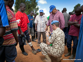 An FDLR rebel shows a gun wound to MONUSCO DDRRR officers as they assess the living conditions of the element who recently surrendered to SADEC in Kanyabayonga MONUSCO base, the 5th of June 2014. © MONUSCO/Sylvain Liechti