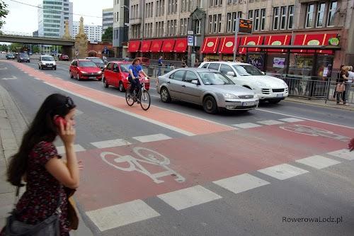Rowerzysta dojeżdżający pasem ruchu do śluzy rowerowej
