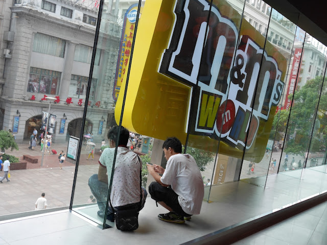 two young men staring out a window while crouched at the M&M's World in Shanghai