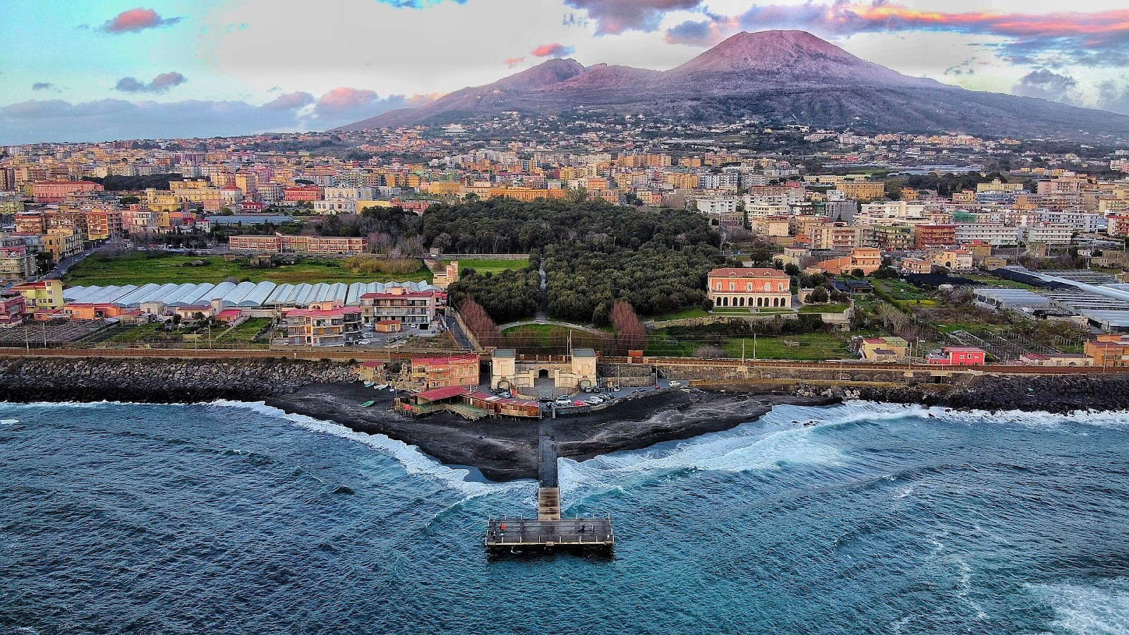 naples dramatic coast small pier sunset skyline traditional buildings mount vesuvius in background italy. Naples is a must-visit city on a Southern Italy road trip.