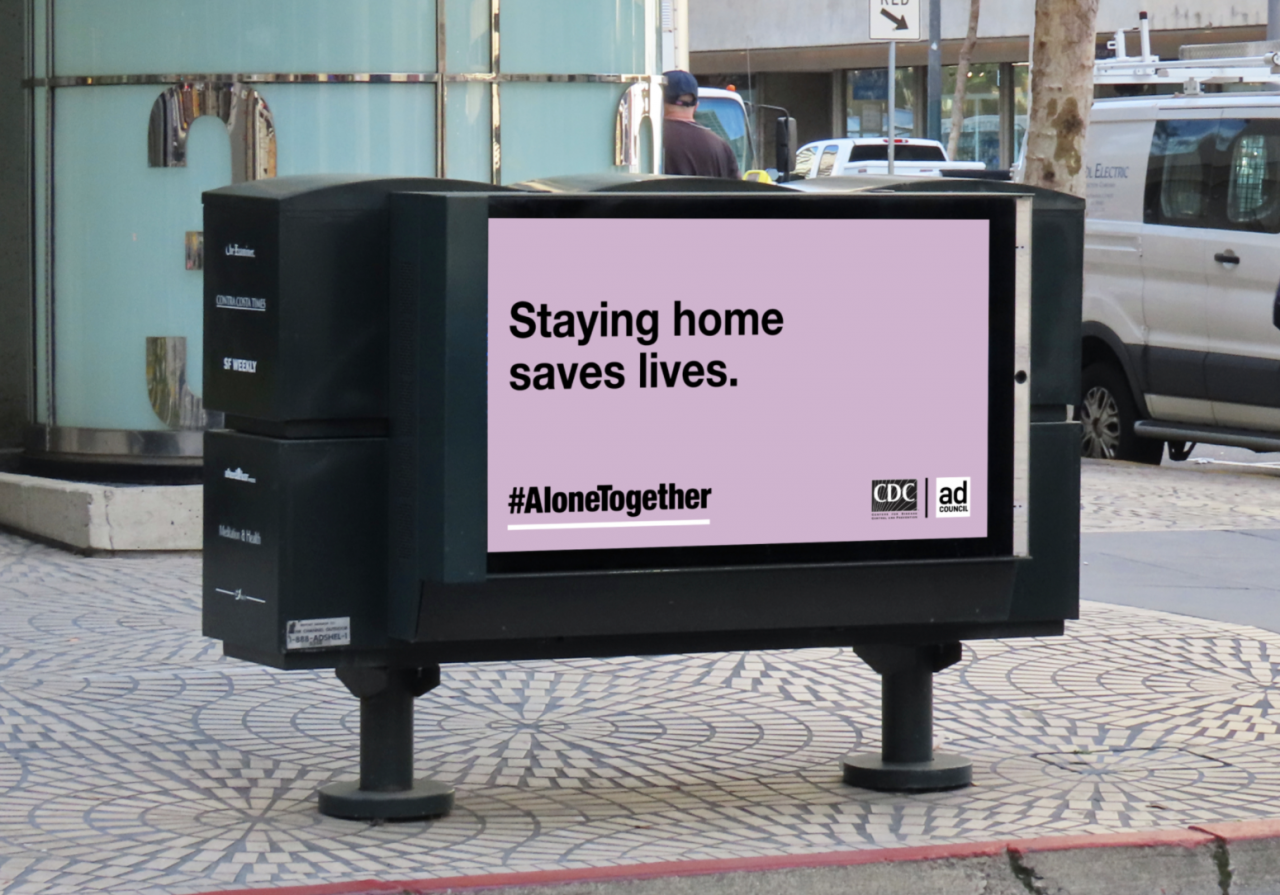 """Billboard with light purple background and black text """"Staying home saves lives."""" and the hashtag #AloneTogether"""