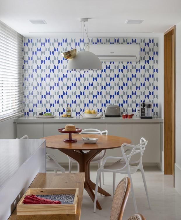 Cozinha com azulejos geométrico em cor cinza e azul, mesa redonda de madeira com cadeira branca, luminária pendente branca e piso porcelanato branco.