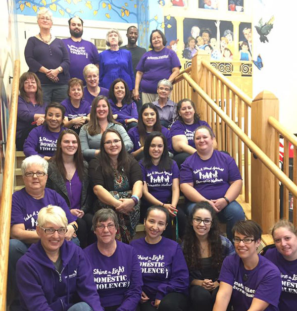 group of community crisis center volunteers in purple shirts sitting on stairs