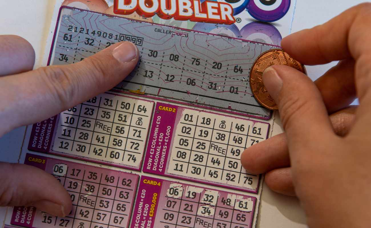 Hand of woman holding coin on Bingo lottery scratch card