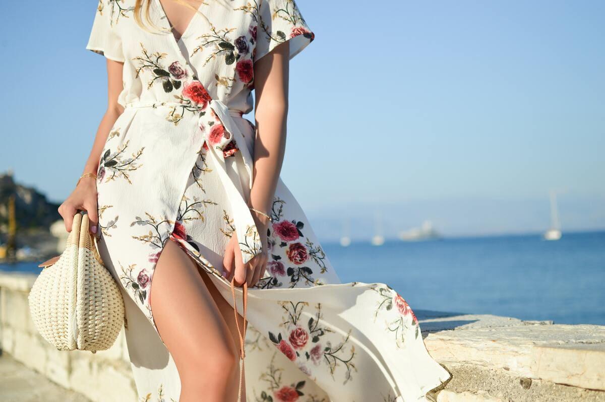 Una ragazza che indossa un vestito bianco estivo corredato con una borsa in paglia bianca