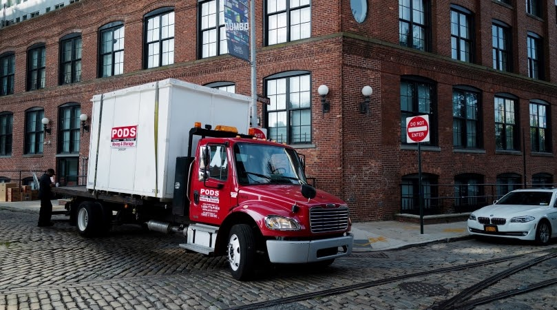 PODS truck delivering a portable storage container in a big city