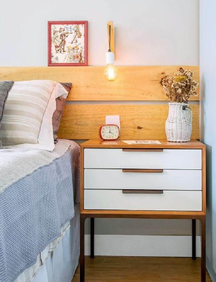 Quarto com decoração rústica minimalista com cabeceira de madeira, criado mudo e piso de madeira.