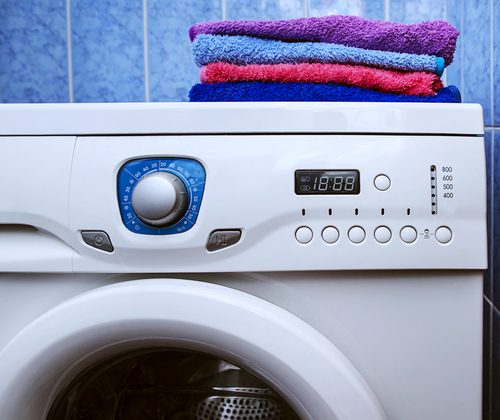 A close up of a front-loading washing machine with a stack of colorful towels on top of it.