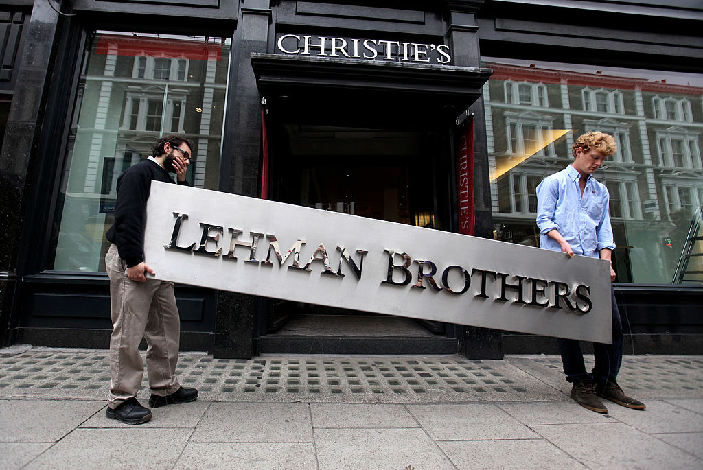Chinese stock. Two employees of Christie's auction house manoeuvre the Lehman Brothers corporate logo, on September 24, 2010 in London, England. Archegos Capital Management's head trader, William Tomita, was formerly a trader at Lehman Brothers. Archegos took big hits when Chinese stock fell after regulatory implementations on March 26.