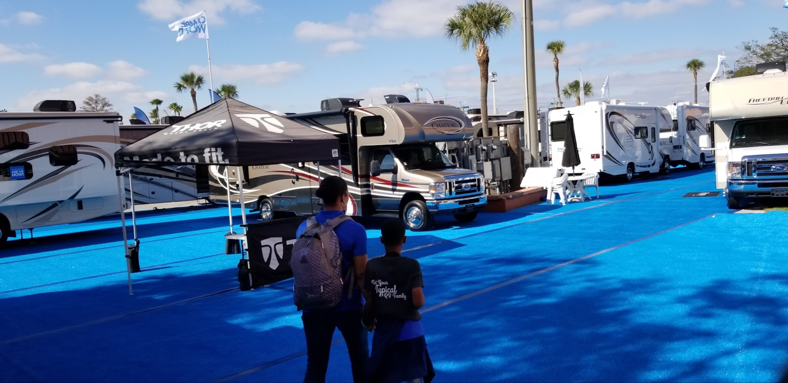 Mother and son explore an outdoor RV show