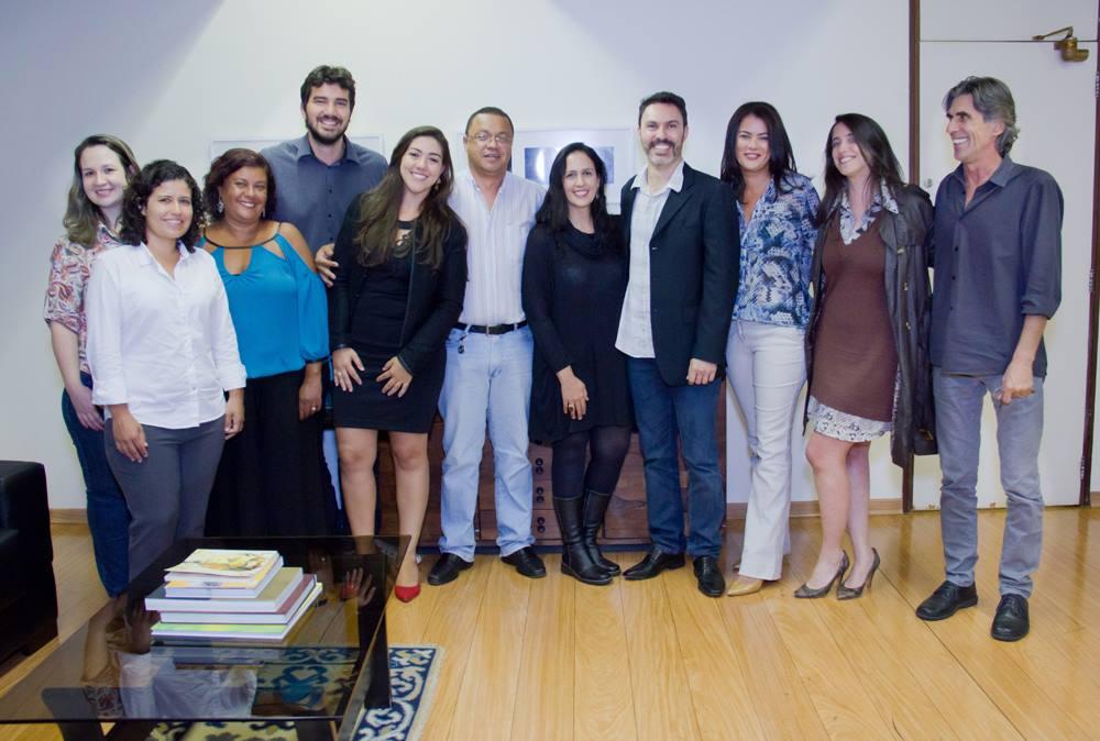 Onze pessoas, participantes da reunião, em pé, sorrindo e posando para a foto. À frente se vê uma mesa de vidro baixa com alguns livros empilhados, sobre um tapete.