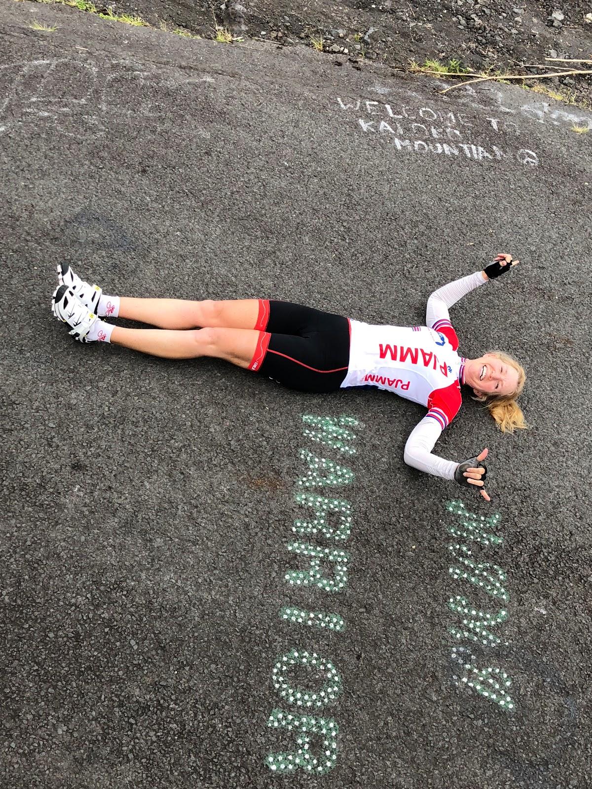 Cyclist on ground next to Mama Warrior roadway sign on Kaloko Drive Hawaii