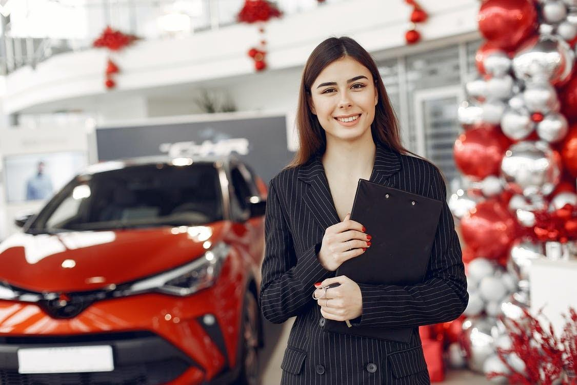 Delighted young female car dealer in car salon