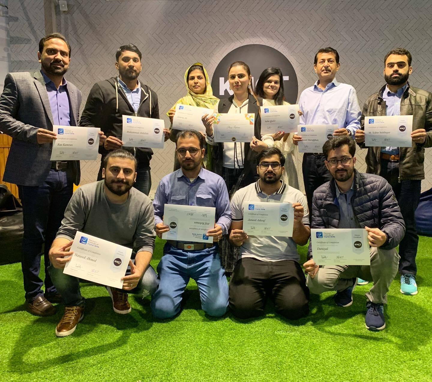Group of employees holding diplomas in their hands.