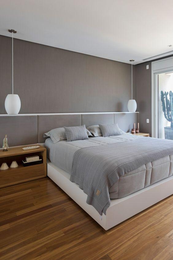 Quarto de casal com decoração em tons neutros, paredes e cabeceira estofada cinza, luminárias pendentes brancas e piso de madeira.