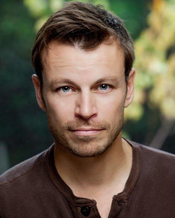 Finlandia te paga por tener bebés; guapo chico finlandés de ojos azules, cabello corto y castaño y barba corta; actor de serie Vikingos, Peter Franzén