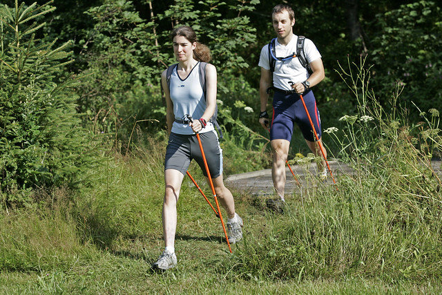 Man and Woman Nordic Walking through grass.