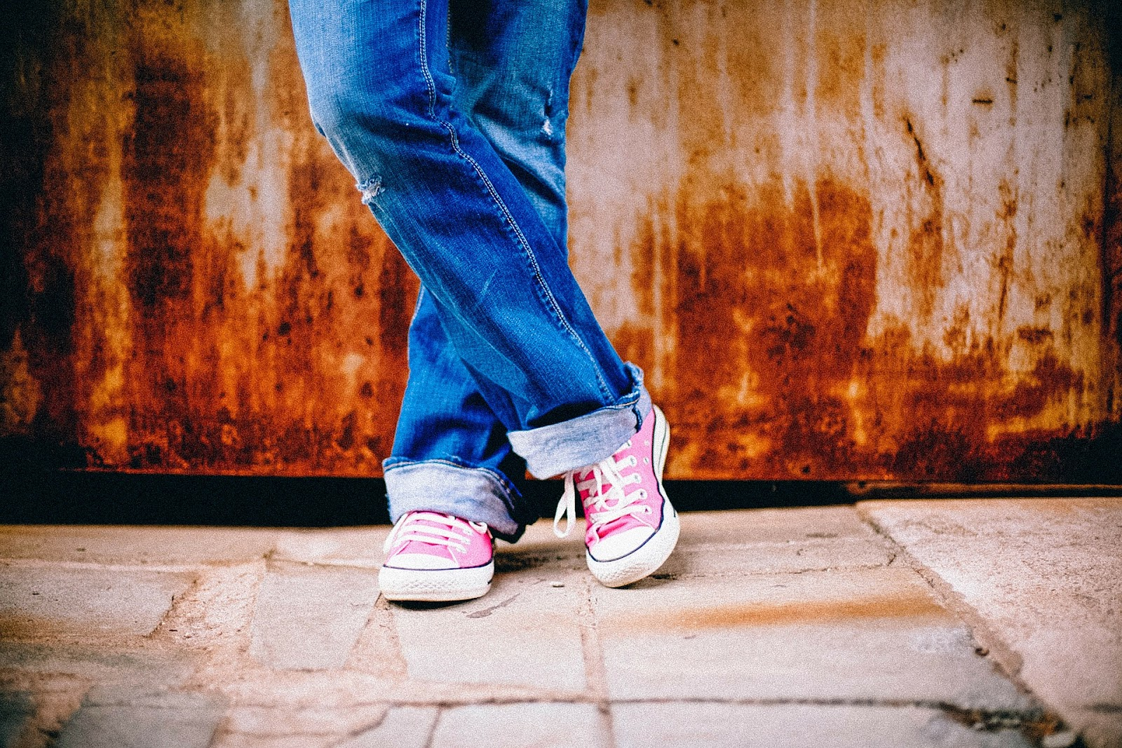 Legs of a person in jeans and pink Converse shoes