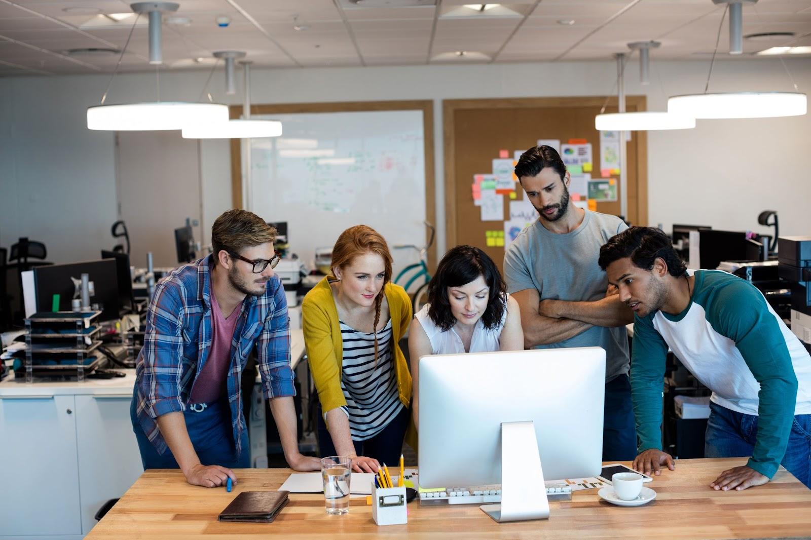 Foto de 5 pessoas, duas mulheres e três homens, todos jovens, em frente à uma tela de computador, demonstrando o trabalho em conjunto realizado por meio de metodologias ágeis.