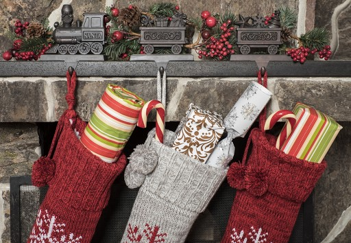 A decorated mantle piece with holiday stockings hanging from it.