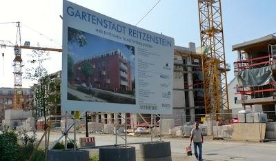 Großbaustelle, Schild: »Gartenstadt Reitzenstein. Hier entstehen 76 Mietwohnungen…«.
