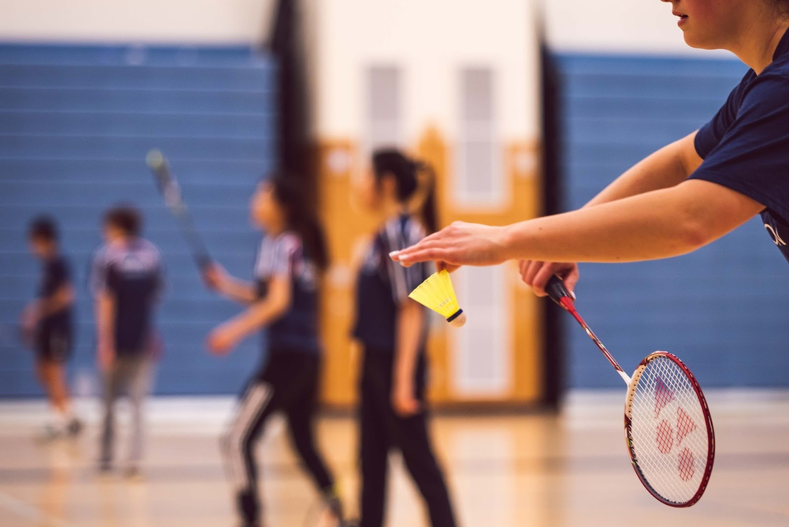 A badminton court has at least eight people on it.