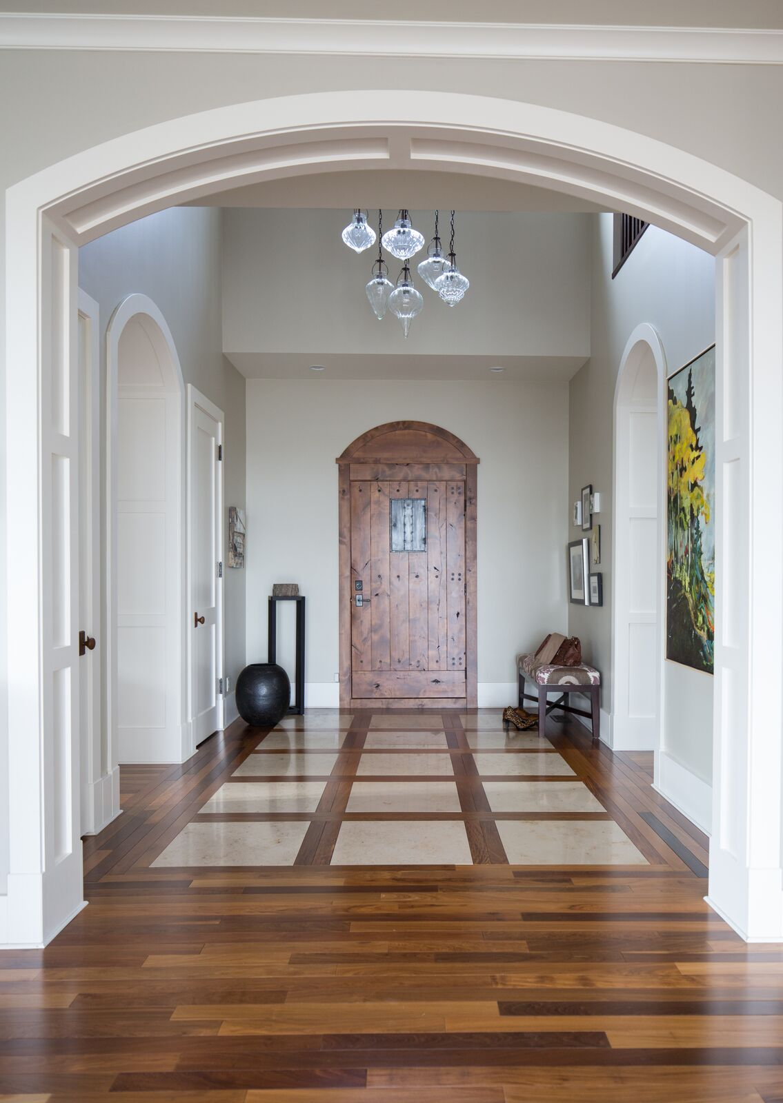 Elegant entryway in Calgary, wooden door, arches, pendant chandelier, taupe bench gallery wall calgary