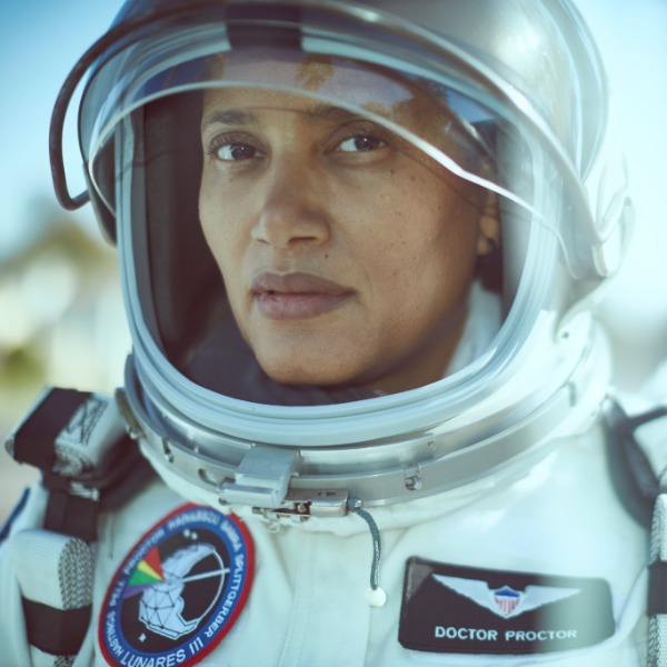 A Black woman (Dr. Sian Proctor) gazes into the camera in a white astronaut suit with her helmet's visor raised.