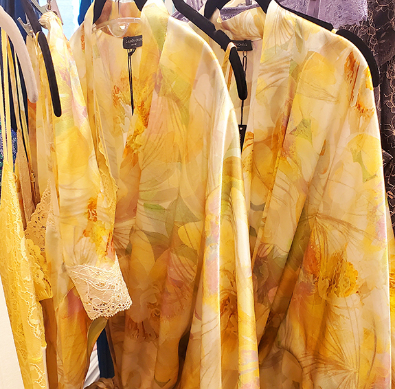 Bright yellow flowery and lacy robes on a hanger.