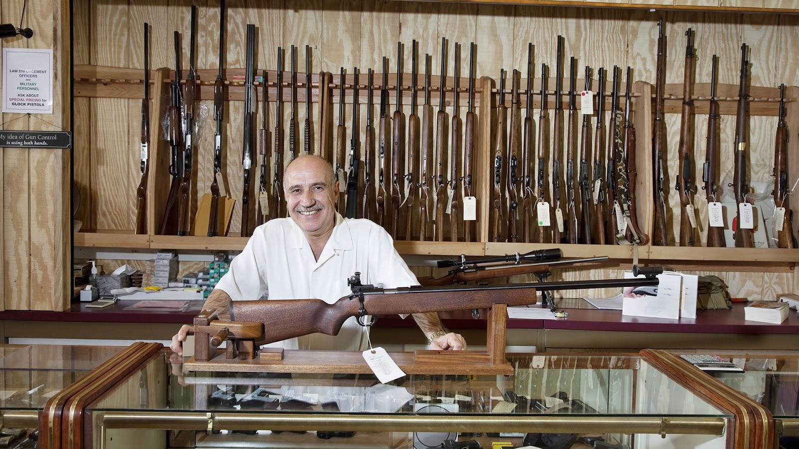 gun store owner showcasing a rifle
