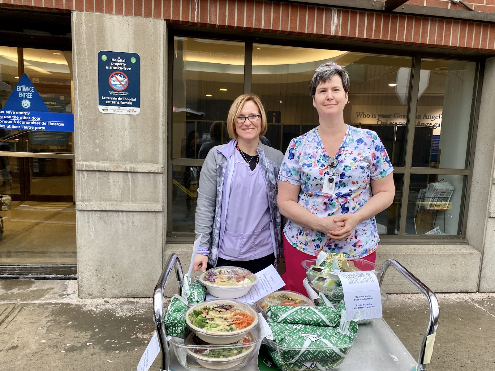 Two middle-aged women serving wrapped food