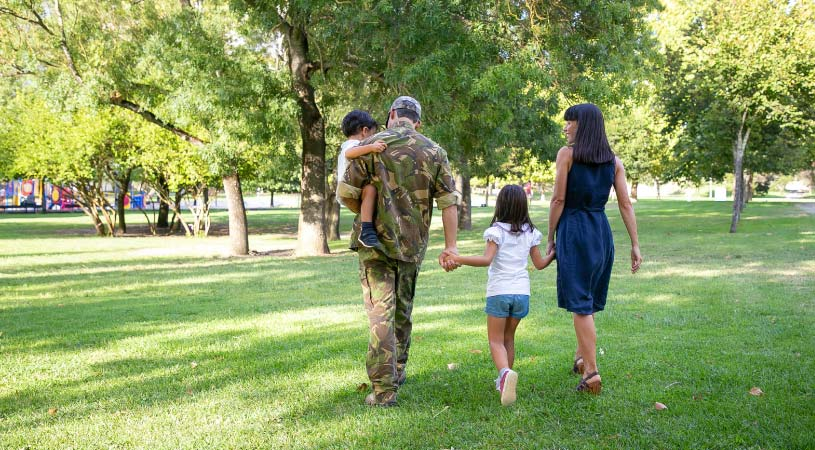 U.S. Army soldier in uniform walking in park with spouse and children