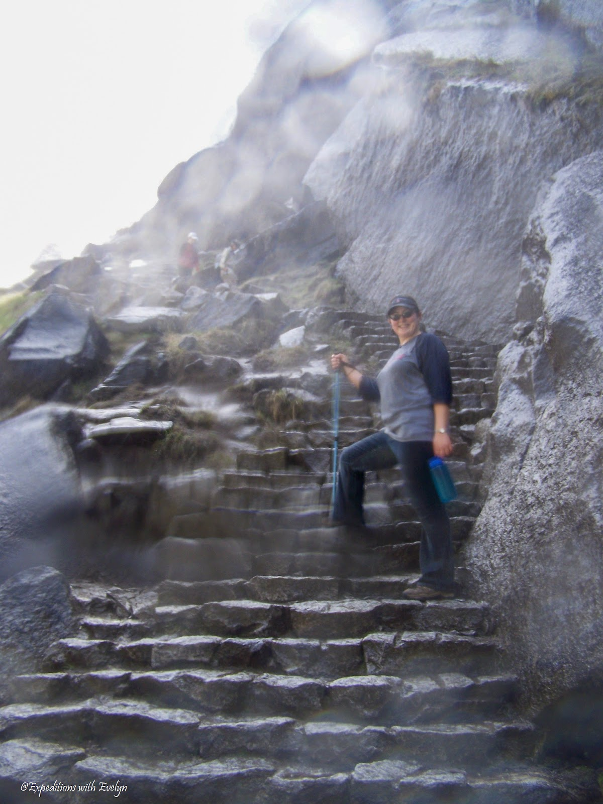 A hiker smiles on the steps of a mist cover trail in the spray of a waterfall.  Water droplets dot the camera lens.