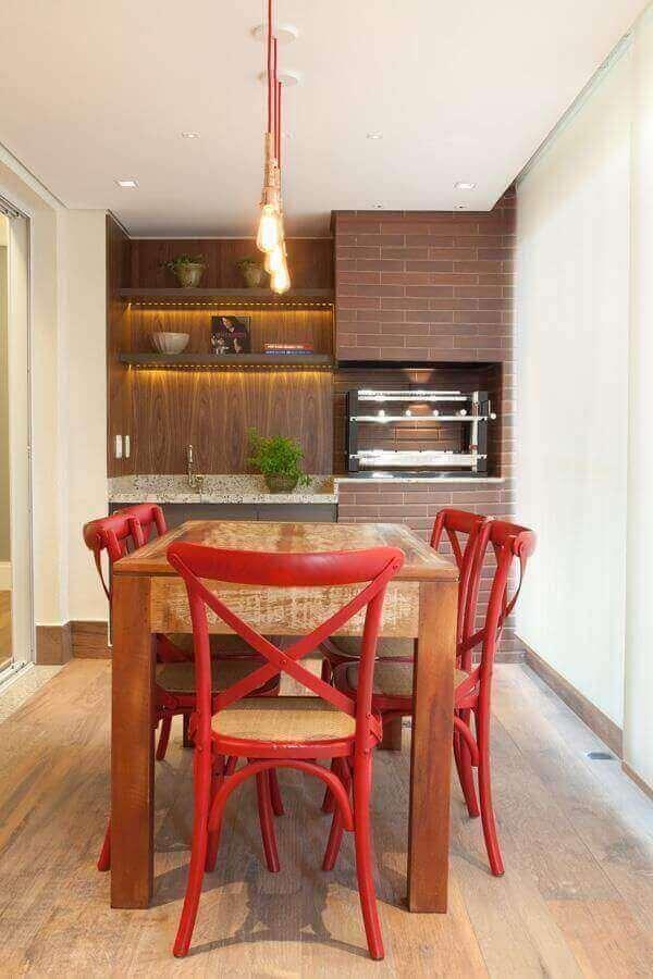 Área gourmet de apartamento com churrasqueira revestida de tijolinhos em tom amadeirado, mesa de madeira com cadeiras vermelha, parede da pia revestida de azulejo amadeirado e piso de madeira.