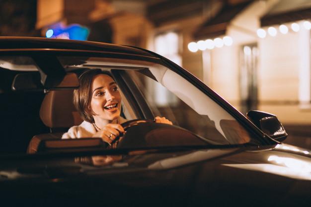 Mulher motorista de aplicativo dirigindo o seu carro a noite