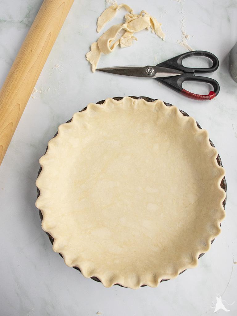 Vegan pie crust dough in pie plate with crimped edges