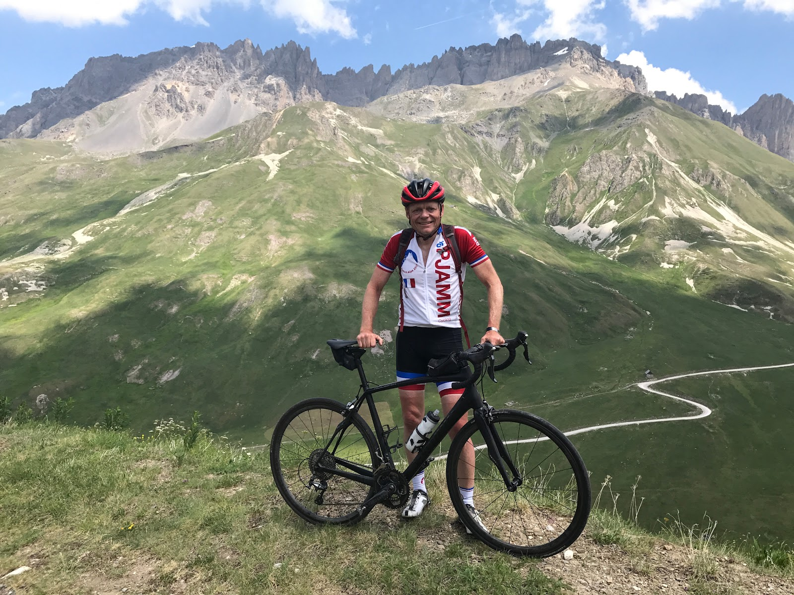 Climbing Col du Galibier - from Valloire by bike - John Johnson of PJAMM with bike and road, mountains in background