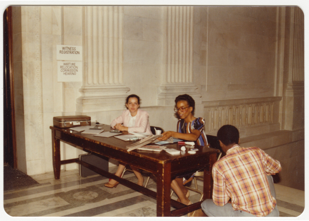"""Three staffers at a desk outside the hearing room. Signs on the wall read """"Witness Registration, Wartime Relocation Commission Hearing."""" Two women are seated at the desk and a man is squatting on the floor with his back turned to the camera."""
