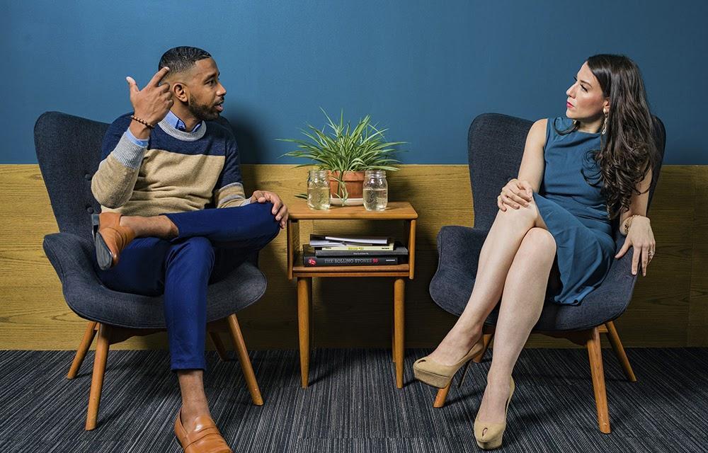 imagem de duas pessoas conversando sentados em cadeiras de escritório