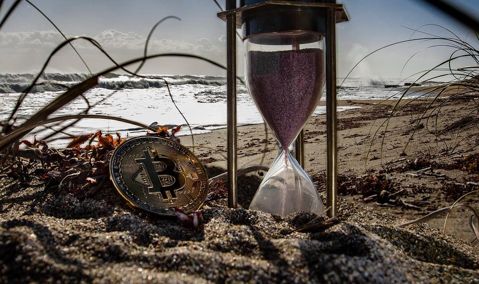 Uma ampulheta e uma moeda de Bitcoin sobre a areia de uma praia.