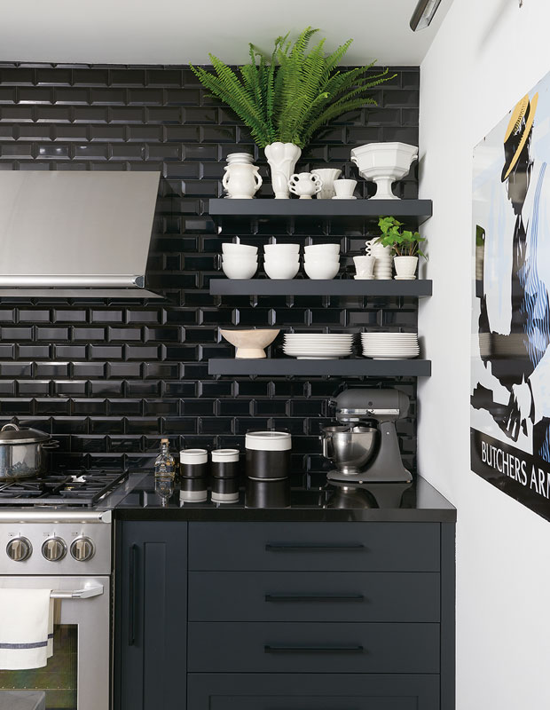 modern kitchen with black subway tile backsplash, floating shelves, navy kitchen cabinets, black hardware and stainless steel appliances