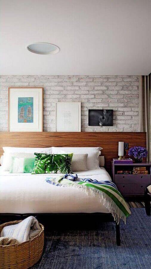 Quarto de casal com cabeceira de madeira e parede de fundo de tijolinhos, criado mudo roxo e quadros decorativos.