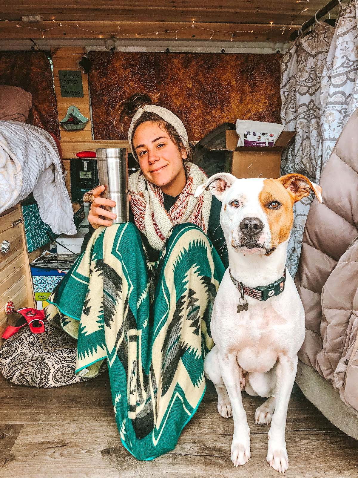 Annie inside of a converted van with a green blanket smiling next to her emotional support dog Henna.