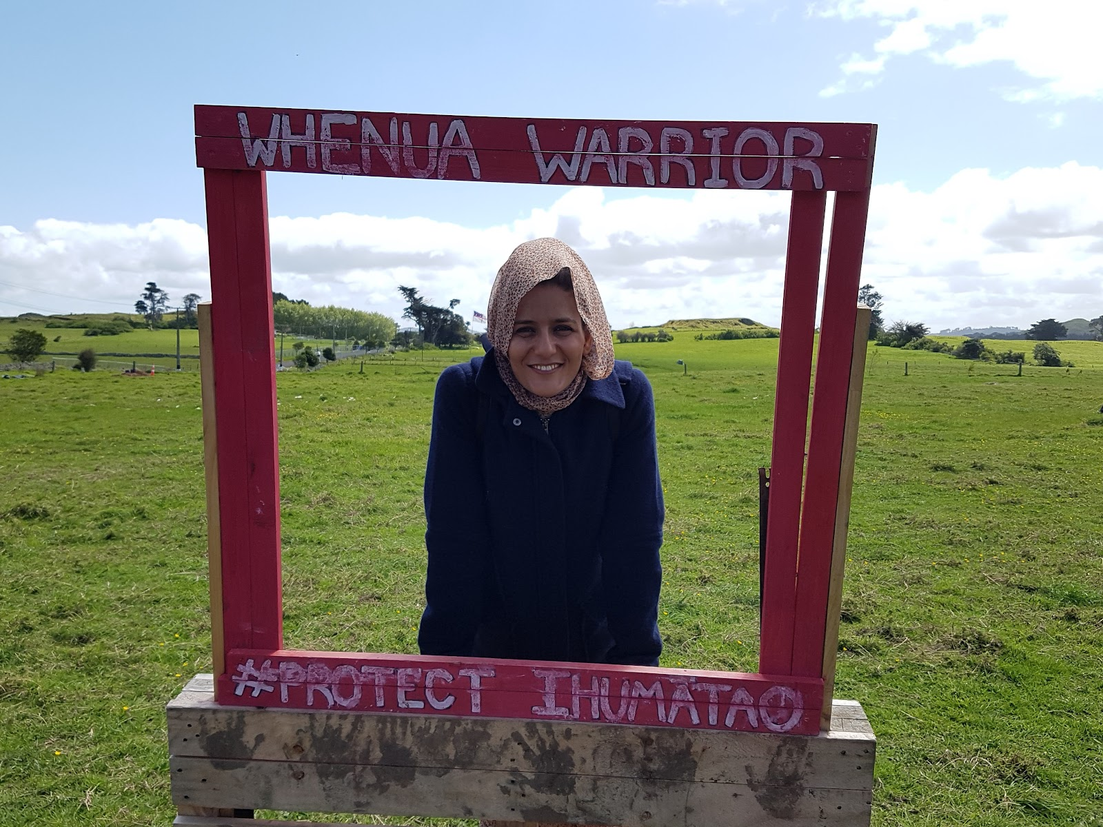 Picture of Tecber Ahmed Saleh at Ihumātao, with backdrop of green grass and cloudy blue sky, photographed through a red wooden frame that reads: WHENUA WARRIOR #PROTECT Ihumātao