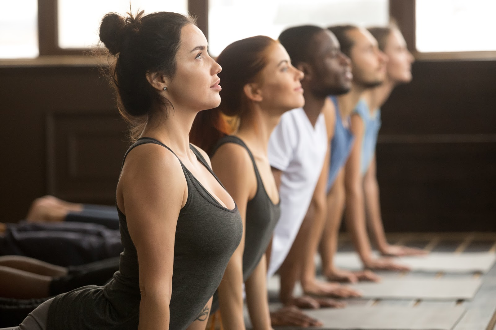 A group of people stretching yoga class