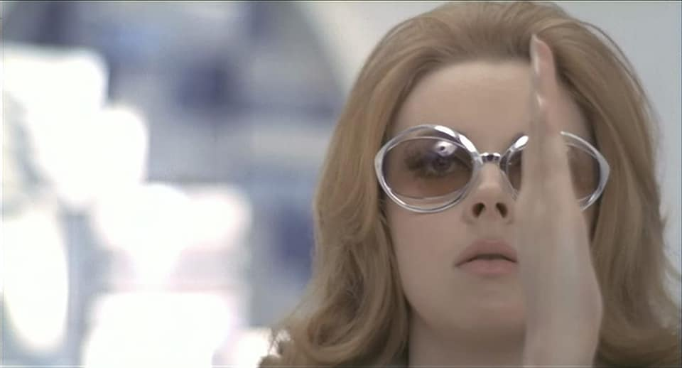 the picture is a still from the ending of the film, depicting Mary in a closeup in focus as parts of her white lair is blurry in the background. She is wearing big oval-shaped sunglasses with silver frames and lightly tinted glass so that her wide-open eyes are still visible through them. Wearing her natural hair, in shoulder length, with some light curls at the end as she has her mouth slightly open and seems to be looking ahead for what's to come. She has her right hand raised in front of her face on the side, which covers her left eye