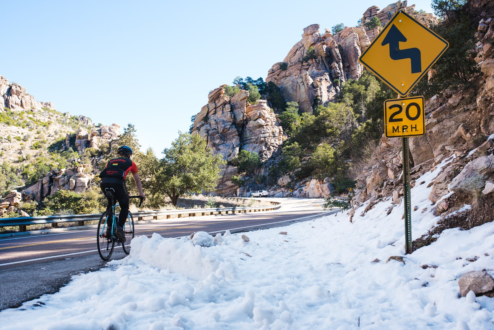 Cyclist riding bike on Mt Lemmon Highway past snow and road sign