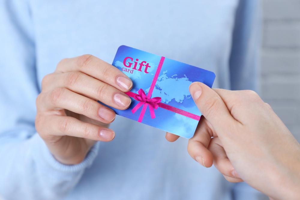 Uma pessoa entregando um gift card para outra pessoa.