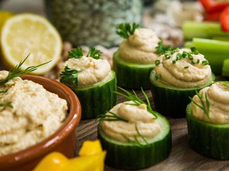 Cucumber topped with hummus is a super healthy snack that beats hunger.