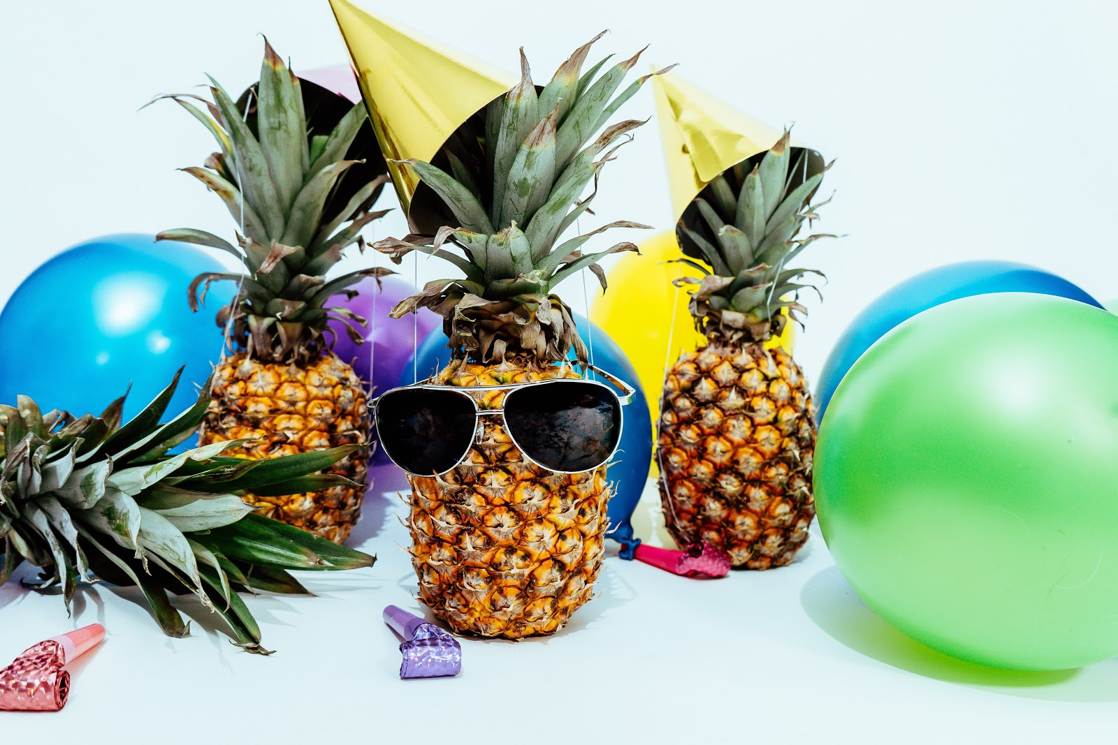 three pineapples with balloons and party hats